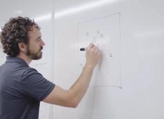 Thomas sketching a diagram on a whiteboard